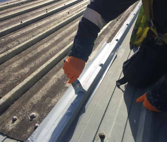 The Topcoat element of the Polyurethane Liquid Application Waterproofing Coating system is applied to roof in repair project for corrosion damage